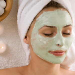 spa facial with green face mask and candles