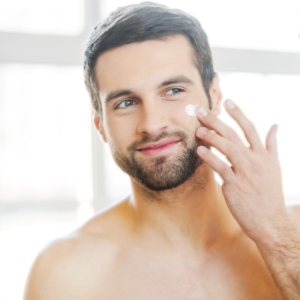 young man applying skin care smiling