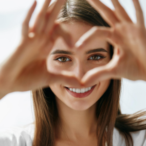 Smiling face framed by hands in heart
